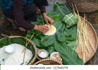 Making (wrapping) Chung Cake, the Vietnamese lunar new year Tet food outdoor with old woman hands and ingredients. Closed-up.