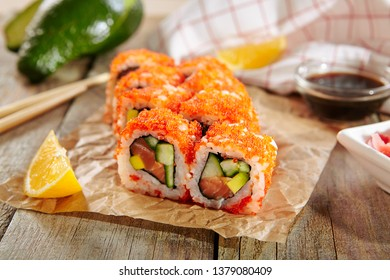 Makizushi Sushi Roll California with Cucumber, Avocado and Salmon on Wooden Rustic Background Close Up. Macro Photo of Nori Maki Rolls with Raw Trout and Red Tobiko Caviar on Grunge Retro Backdrop