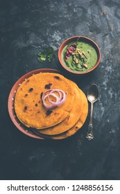 Makki di roti with sarson ka saag, popular punjabi main course recipe in winters made using corn breads mustard leaves curry. served over moody background. selective focus