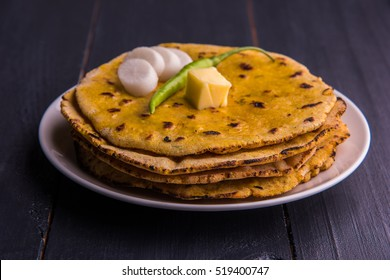 Makki Ki Roti with ghee or Corn floor flat bread is a Punjabi food usually served with Sarson Ka Saag. Served in white plate over moody background. selective focus