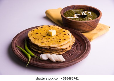 Makki Ki Roti & Sarson Ka Sag is basically Corn floor flat bread & curry using mustard greens respectively. Popular Punjabi food. Served in wooden bowl and plate over moody background. selective focus