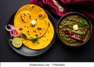 Makki Ki Roti & Sarson Ka Sag is basically Corn floor flat bread & curry using mustard greens respectively. Popular Punjabi food. Served in a bowl and plate over moody background. selective focus