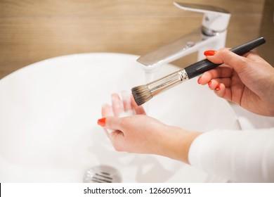 Faire des brosses. La femme qui lave la brosse sale se maquille avec du savon et de la mousse dans l'évier.