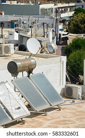 MAKRIGIALOS, CRETE - SEPTEMBER 18, 2016 - Water heating solar panels on a building roof, Makrigialos, Crete, Greece, Europe, September 18, 2016.