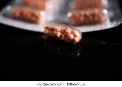 Makro close up of capsule pills in silver blister package and one isolated capsule with black reflecting background. Transparent shell showing pearls like ingredients. (Focus isolated capsule)