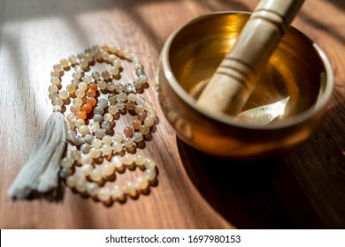 Mala beads and a golden Tibetan bowl on a wooden background in the soft and beautiful light of morning, a perfect time for a yoga session acompanied by healing sounds.