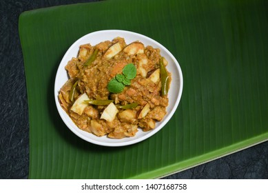 Malabar style Kozhi Pidi or Kunji Pathal is soft rice dumplings cooked in roasted coconut chicken curry. Popular South Indian meal, snack or side dish served on banana leaf in Kerala India.