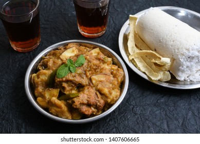 Malabar style Kozhi Pidi or Kunji Pathal is soft rice dumplings cooked in roasted coconut chicken curry with Indian black tea, Puttu. Popular meal, snack, side dish in dark background in Kerala India.