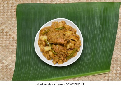Malabar style Kozhi Pidi or Kunji Pathal is soft rice dumplings cooked in roasted coconut chicken curry. Popular meal, snack or side dish on green banana leaf background in Kerala India.