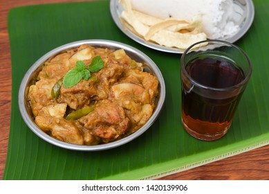 Malabar style Kozhi Pidi or Kunji Pathal is soft rice dumplings cooked in roasted coconut chicken curry with Indian black tea. Popular meal, snack or side dish in banana leaf background Kerala India.