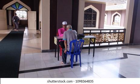 Malacca, Malaysia; 25/05/2018; Muslim man paying the zakat as the obligation for every muslim during ramadan at Al Azim Mosque, Malacca, Malaysia.