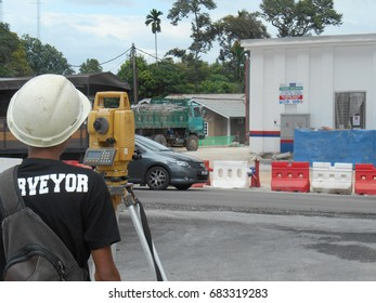 MALACCA, MALAYSIA -APRIL 21, 2016: Surveyor with survey equipment at the construction site. He using this equipment to determine and check level.