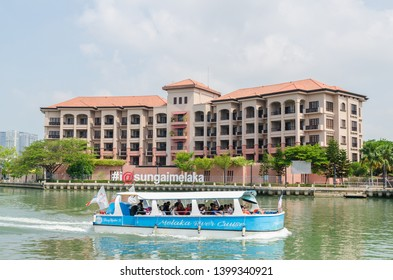 Malacca, Malaysia - April 21, 2019:  Riverside scenery of a cruise full of passengers crossing by the Malacca River. It has been listed as UNESCO World Heritage Site since 7/7/2008.