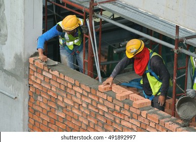 MALACCA, MALAYSIA -AUGUST 24, 2016: Construction workers laying brick to form brick wall at the construction site.