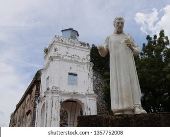 Malacca, Malaysia-- February 2018: Armless statue of St. Francis Xavier with the ruins of St. Paul's Church building in Malacca City.