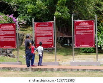 Malacca, Malaysia-- February 2018: A man and two boys reads the Informational billboards at the Fort terrace of A Famosa Portugese fortress in Malacca City.