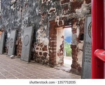 Malacca, Malaysia-- February 2018: Medium close up of old tombstones lining up along the walls of St. Paul's Church ruins in Malacca City.