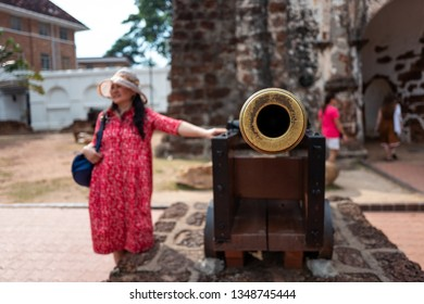 Malacca, Malaysia - February 28, 2019: Asian tourist puts her hand on old canon in Malacca old city.