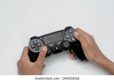Malacca, Malaysia - January 16 2019. Close up gamer's hands are controlling PS 4 controller. PS 4 is the 8th generation home video game console developed by Sony Interactive Entertainment.