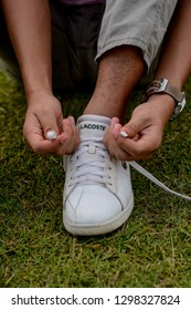 Malacca, Malaysia - January 29 2019. Close up a man is tying his Lacoste white shoe.