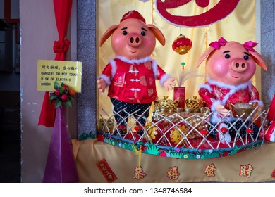 Malacca, Malaysia - March 01, 2019: Pig statues with warning sign in temple.