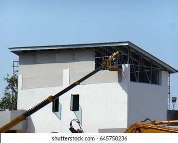 MALACCA, MALAYSIA -MARCH 16, 2017: Construction workers standing in the mobile crane bucket while working at high level in the construction site. The bucket movement controlled by the workers himself.