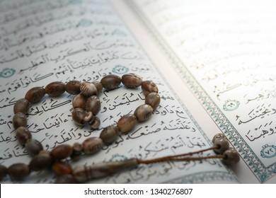 Malacca, Malaysia- March 16 2019. Closeup tasbih (beads) over the Holy Koran verse. Holy Koran is the greatest book in Islam.