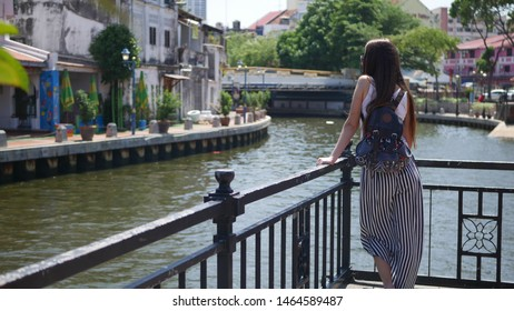 Malacca, Malaysia - May 10 2019: tourist girl on the quay of Malacca river. Is an old historical place, the center of city was listed by UNESCO as a World Heritage Site