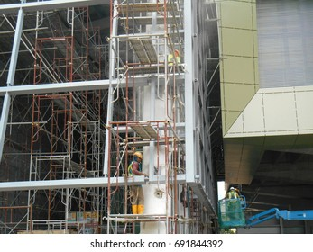 MALACCA, MALAYSIA -MAY 29, 2017: Construction workers used metal scaffolding when working at height at the construction site. They are required to wear necessary safety equipment to do so.