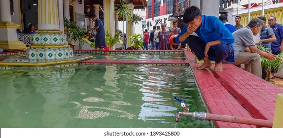 MALACCA, MALAYSIA - May 9, 2019 : Unidentified Muslim wash body parts using water before performing prayer. This ritual purification known as wudu' or ablution is a must before performing a prayer.