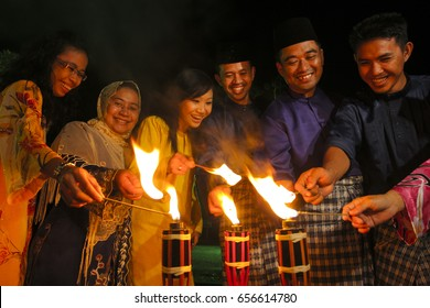 MALACCA, MALAYSIA - SEPTEMBER 10, 2008 : Men and woman light up the Malay tradition oil lamp or pelita during Hari Raya celebration.