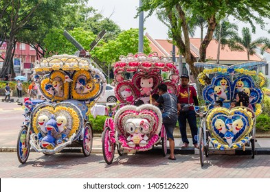 Malacca,Malaysia - April 21,2019 : The colorful decorated rickshaws are parking in Dutch Square Malacca waiting for customers.Malacca has been listed as a UNESCO World Heritage Site since 7 July 2008.