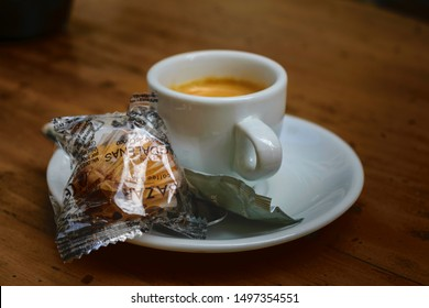 Malaga, Andalusia / Spain - August 22 2019. Selective focus close up view of an expresso cup with a small packed cake, sugar and spoon served at a cafe terrace in the historical city center.