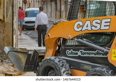 Malaga, Andalusia / Spain - July 26 2019. Orange skid steer loader in action in a city center carrying gravels with pedestrians on the walkway in the background