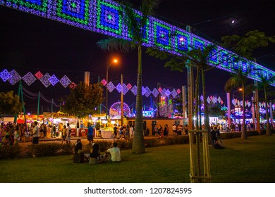 The Malaga fair at night, Feria de Malaga. People enjoying the fair attractions and night lights.