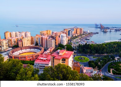 Malaga, Spain. Aerial view of the city center at sunset with bullring arena and mediterranean se in Malaga, Spain. City skyline with popular landmarks in the evening