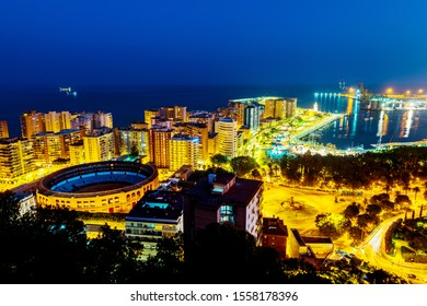 Malaga, Spain. Aerial view of the city center at sunset with bullring arena and mediterranean se in Malaga, Spain. City skyline with popular landmarks at night