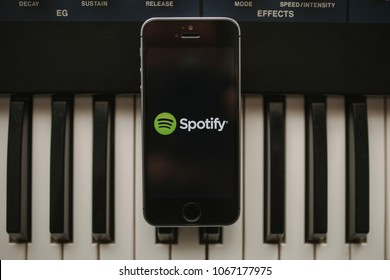 MALAGA, SPAIN - APRIL 12 th, 2018: Spotify Streaming music app in an iPhone screen, placed on a vintage musical keyboard, on April 12, 2018 in Malaga, Spain.