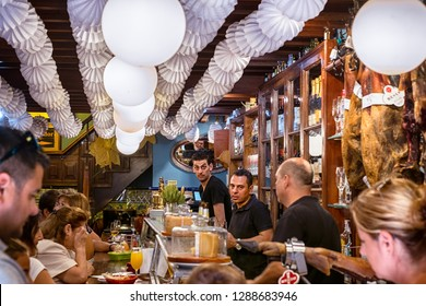 Malaga, Spain - August 12, 2018. People drinking and eating at traditional tapas bar with dry-cured ham legs and vintage decor in Malaga city, Spain