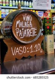 Malaga, Spain. Circa February 2016. Vendor in Malaga Atarazana market sells local wine by the glass from vintage wine barrel.