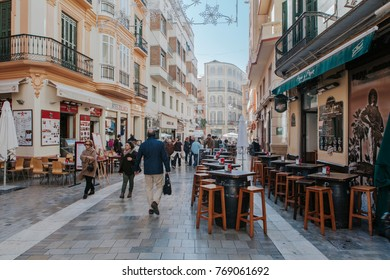 MALAGA, SPAIN - DECEMBER 5th, 2017: View of Malaga city center life, with people walking in the street and shops and restaurants around it, on December 5th, 2017.
