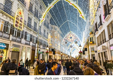 MALAGA, SPAIN - DECEMBER 9, 2017: Crowds of people walking on Calle Marques de Larios street, decorated with Christmas decorations. Most popular pedestrian street of Malaga, Andalusia, Spain