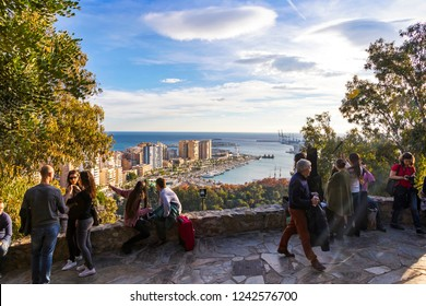 MALAGA, SPAIN - DECEMBER 9, 2017: People enjoy sunny day at Gibralfaro viewpoint (Mirador de Gibralfaro) in Malaga city, Andalusia, Spain. Skyline aerial view of Malaga