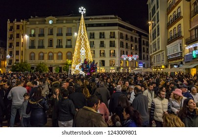 MALAGA, SPAIN - DECEMBER 9, 2017: Crowds of people walking near the decorated Christmas Tree on Plaza de la Constitucion in center of Malaga city, Andalusia, Spain