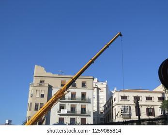 Malaga, Spain - December12, 2018: Large yellow crane at construction site for new Malaga metro againsh blue sky