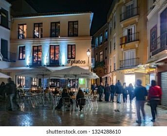 MALAGA, SPAIN - FEB 22-2019: Group of relaxing people drinking at outdoor restaurant in traditional spanish style on February 22, 2019