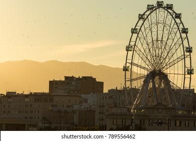 """MALAGA, SPAIN - JANUARY 01, 2018:Looking towards the Ferris Wheel Called """"Malaga Big Wheel"""" (""""Noria de Malaga""""). Andalusia, Spain."""