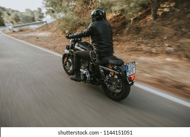 Malaga, Spain - July 15, 2018: Man riding his Harley Davidson motorcycle during a journey trip around Malaga mountain roads in Spain.
