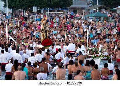 MALAGA, SPAIN - JULY 16: Unidentified local worshipers carry a religious image on a boat during the 'Virgen del Carmen' festival on July 16, 2011 in Malaga, Spain.