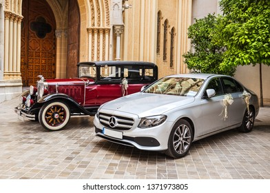 Malaga, Spain - June 16, 2018: Two cars, modern and antique, decorated with wedding paraphernalia, stand at the entrance to the church in Malaga. Spain